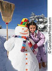 Girl next to snowman