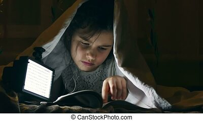girl night reading book under covers with flashlight - girl...