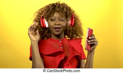 Girl of african american appearance in headphones sings songs. Yellow background
