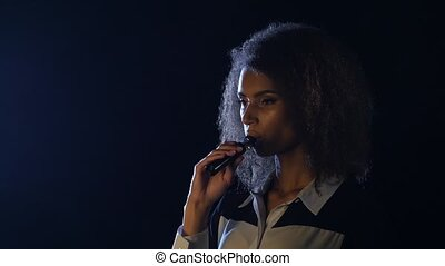 Girl of african american appearance smokes an electronic...
