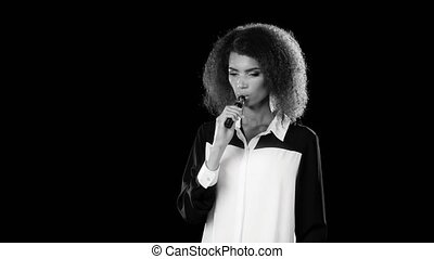 Girl of african american appearance smokes an electronic cigarette. Black background