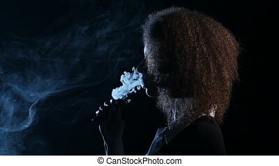 Girl of african american appearance smokes an electronic cigarette. Black background. Side view. Silhouette. Slow motion