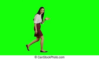 Girl of asian appearance goes to work and waves her hand. Green screen. Side view