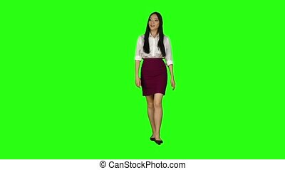 Girl of asian appearance goes to work and waves her hand. Green screen. Slow motion