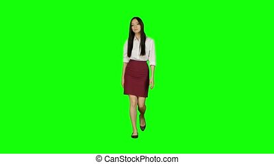 Girl of asian appearance goes to work and waves her hand. Green screen