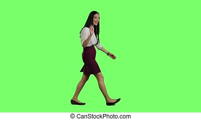 Girl of asian appearance goes to work and waves her hand. Green screen. Side view. Slow motion