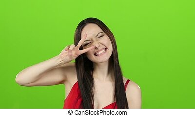 Girl of asian appearance has fun and makes different grimaces. Green screen. Slow motion