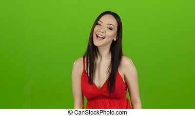 Girl of asian appearance has fun and makes different grimaces. Green screen