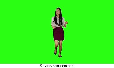 Girl of Asian appearance with a phone is running to an...