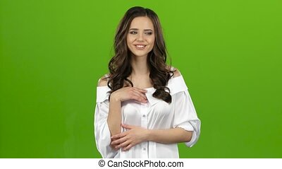 Girl of sends kisses to others, waves her hand. Green screen...