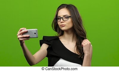 Girl of with a smartphone in her hands makes selfie. Green screen