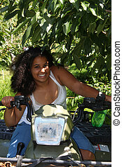 Beautiful teenage girl of Indian descent on a 4 wheeler in the great outdoors