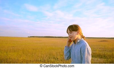 Girl on a background of blue sky are on the road and talking on the phone
