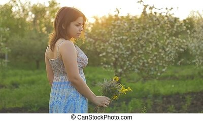 girl on a background of flowering trees at sunset slow motion video