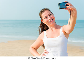 girl on a background of the sea with a small camera