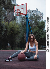 Girl on a basketball court with a ball. Sportswear dressed in leggings and top.