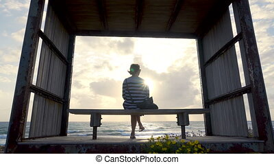 Girl on a bench by the seashore on sunset