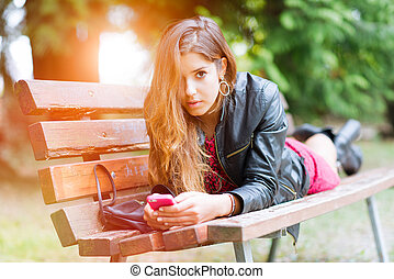 Girl on a bench he writes on his smartphone