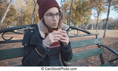 Girl on a bench in the park eating Burger. Girl in a jacket and hat