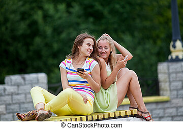 Girl on a bench with phones