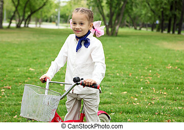 Girl on a bicycle in the green park