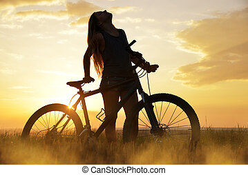 Girl on a bicycle in the sunset.