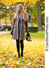 Girl on a fall day, with her shoes in hand