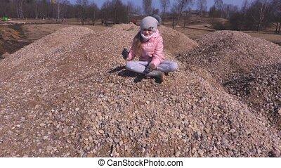 Girl on a gravel pile