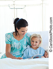 Girl on a hospital bed reading with her mother
