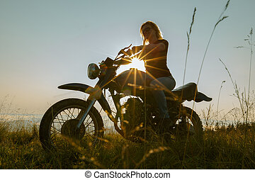 girl on a motorcycle travels in the mountains
