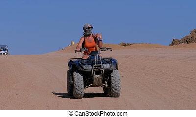 Girl on a Quad Bike Rides through the Desert of Egypt on...