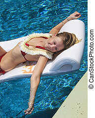 girl on a raft in a pool