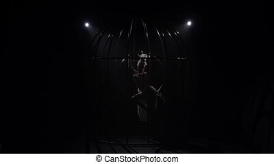 Girl on a rotating hoop in a cage in a dark room. Black background. Silhouette. Slow motion