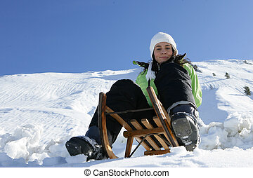 Girl on a sled in mountain