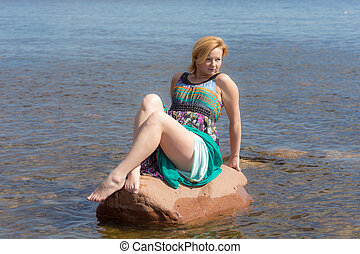 girl on a stone in the water