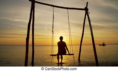 Girl on a swing by the seashore on sunset
