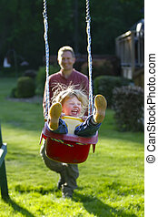 Girl on a Swing - Young blond girl on a backyard swing, ...