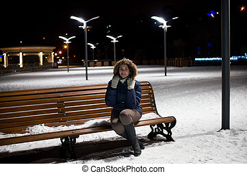 Girl on a winter night sitting on a bench