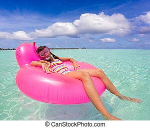 Girl on air mattress in sea