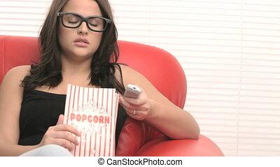 girl on an armchair watching tv