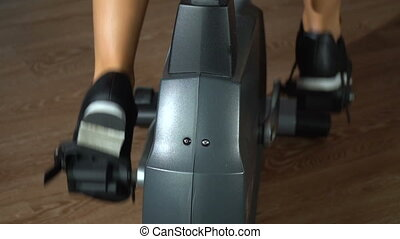 Girl on an exercise bike. Slow motion - Beautiful girl is...