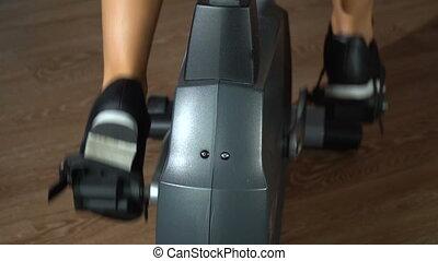 Girl on an exercise bike. Slow motion - Beautiful girl is...