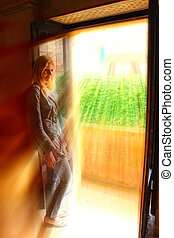 Girl on balcony of the house in golden rays of sun