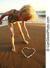 girl on beach - mussels heart at coast with young girl