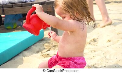 Girl on beach playing with watering pot - Little girl in cap...