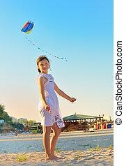 Girl on beach with kite