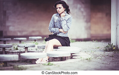 Girl on bench in denim jacket