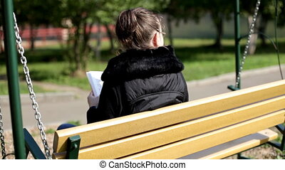 Girl on bench read a book in autumn park
