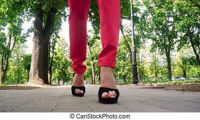 girl on black high heels walking down the street