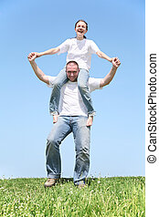 girl on boy\'s shoulders on grass